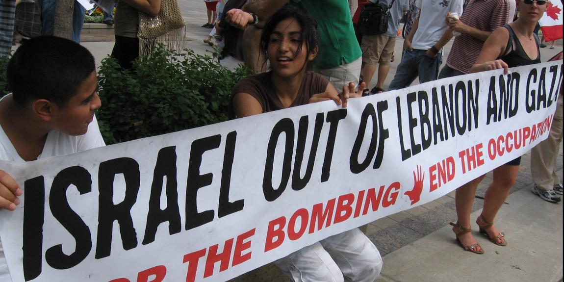"""Israel out of Lebanon and Gaza. Stop the bombing. End the occupation"" lukee nuorten pitämässä banderollissa."